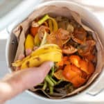 Overhead view of fruit and vegetable scraps in a white container, ready to go in the compost