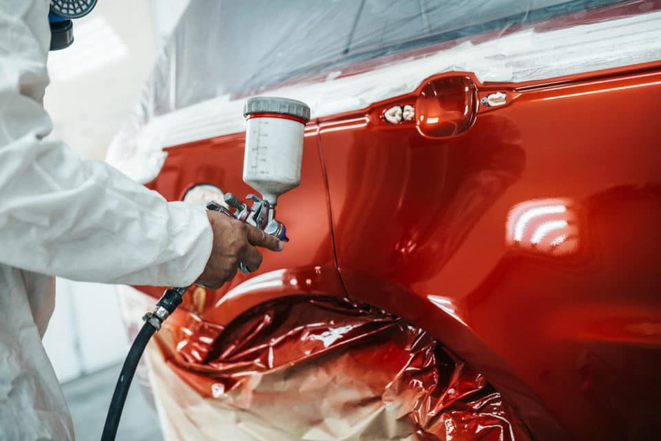 Man with protective clothes and mask painting car using spray compressor.