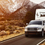 White 2019 RAM 1500 tows large white camper trailer with mountains in background