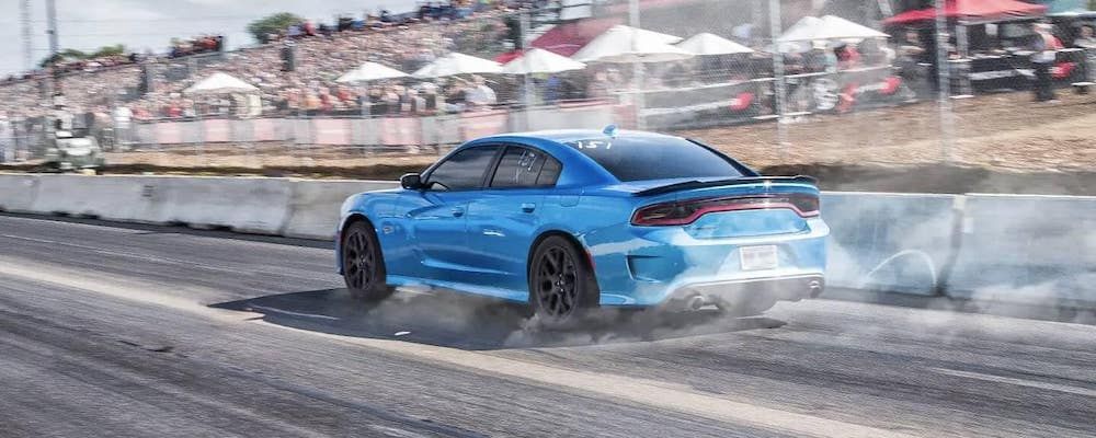 Blue 2019 Dodge Charger tearing down race track with blurred crowd background