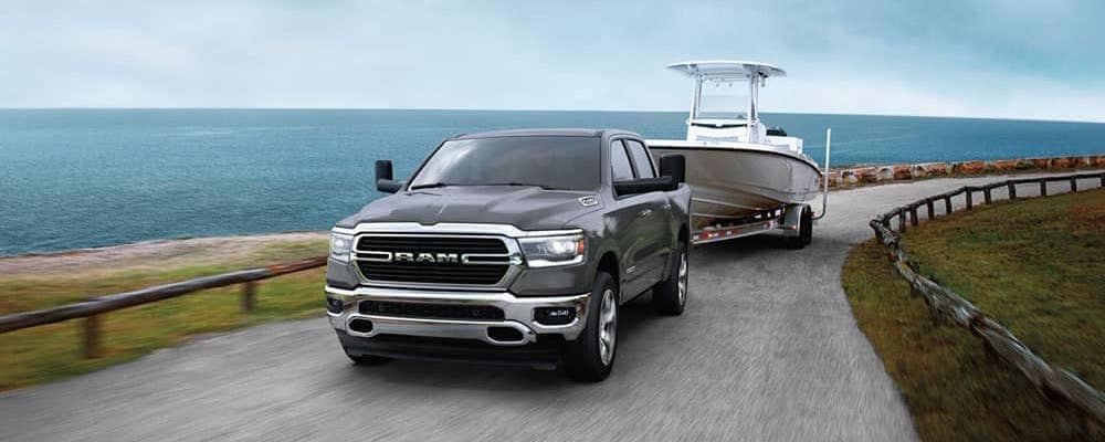2020 RAM 1500 towing a white boat in front of lake