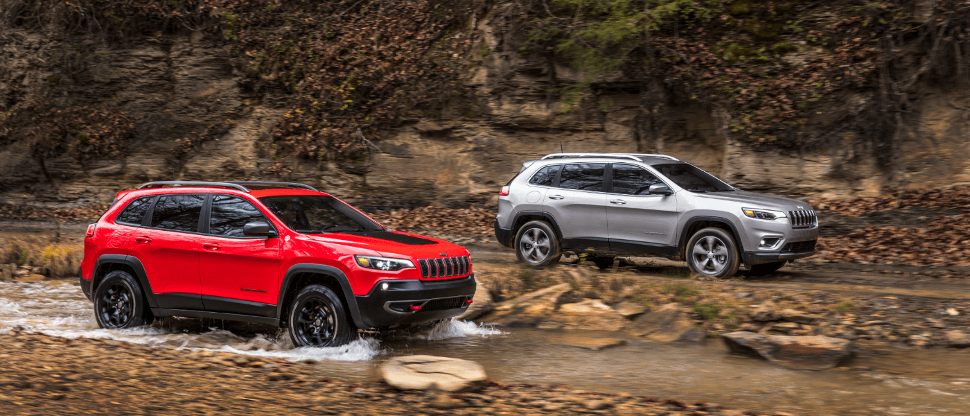 Two 2021 Jeep Cherokees driving through a stream