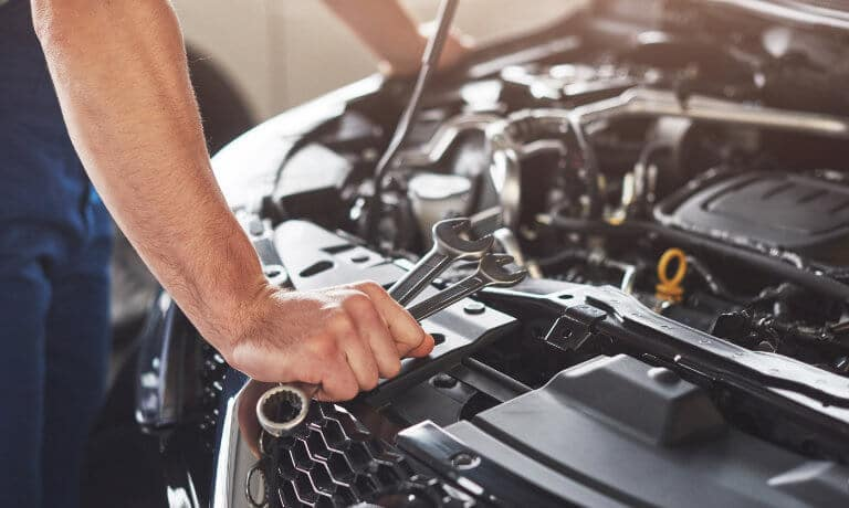 Service technician working under hood of vehicle close up