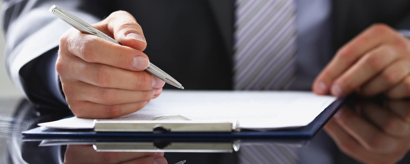 man signing finance paperwork