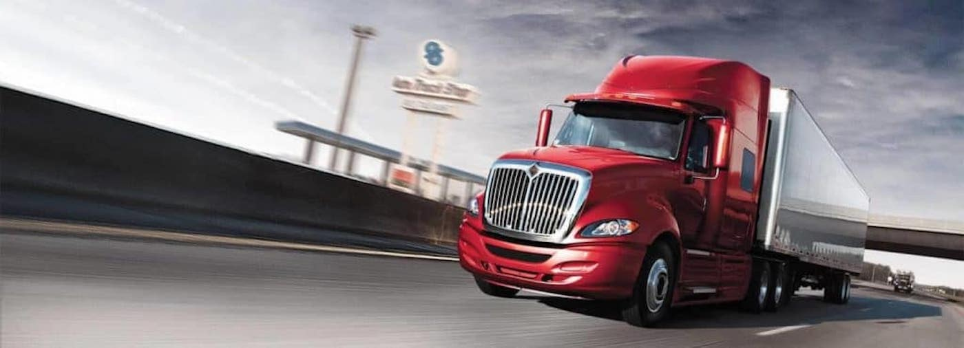 red semi truck driving on road