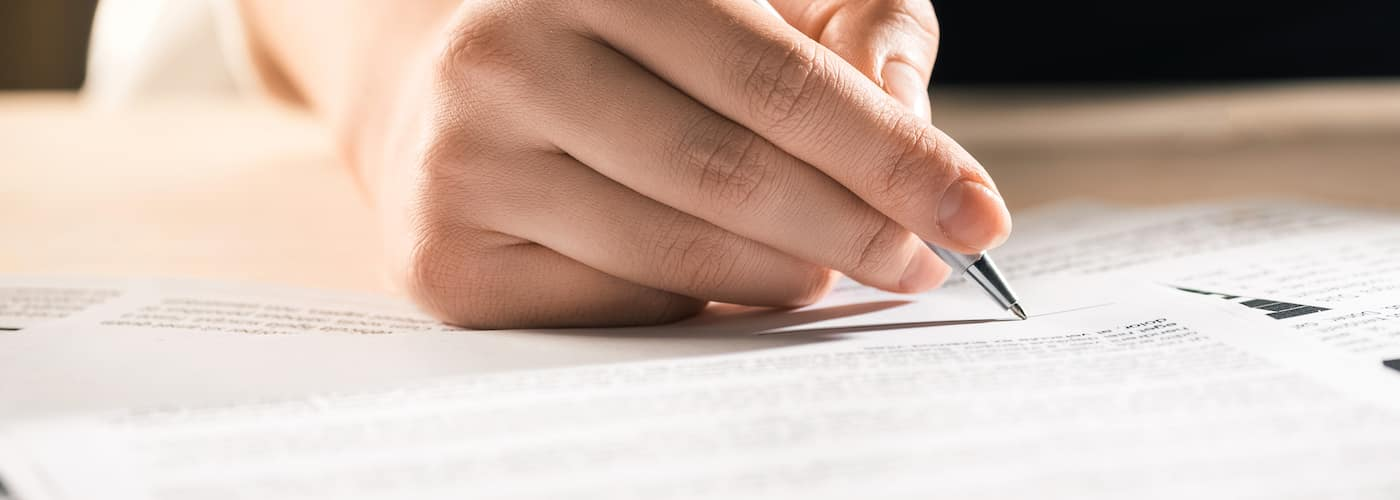 hand closeup signing or writing on documents