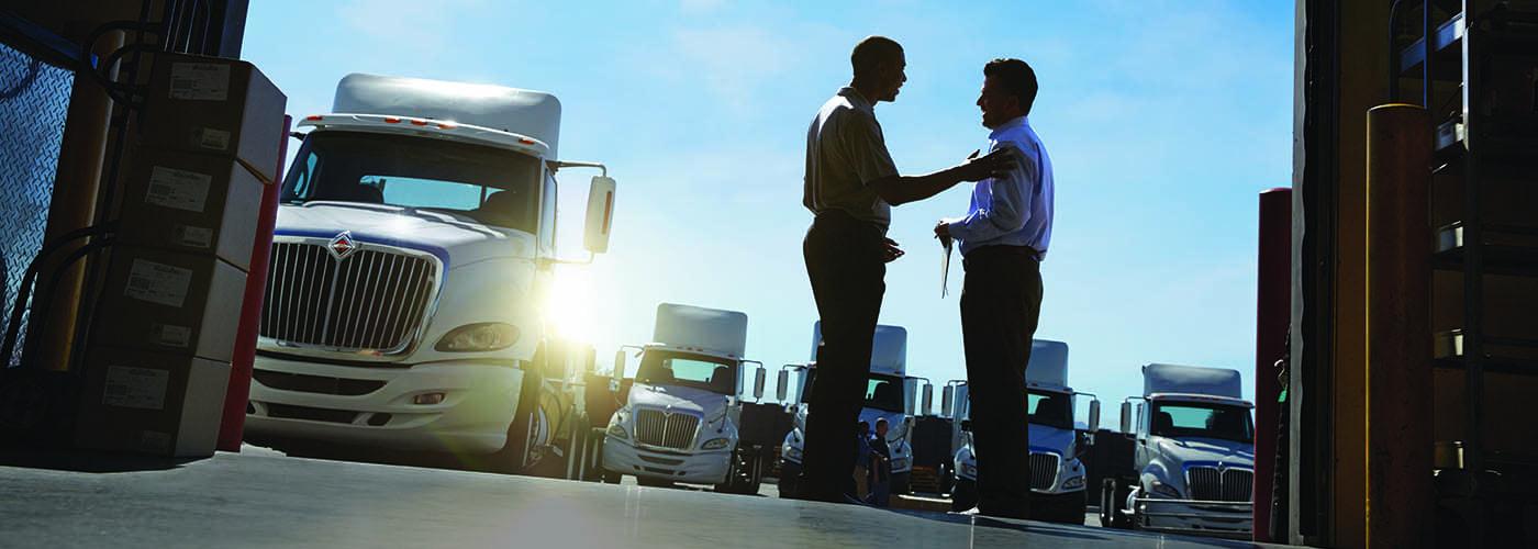 2 men standing in garage by semi truck
