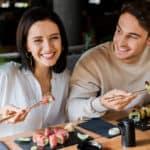 Happy couple eating sushi with chopsticks