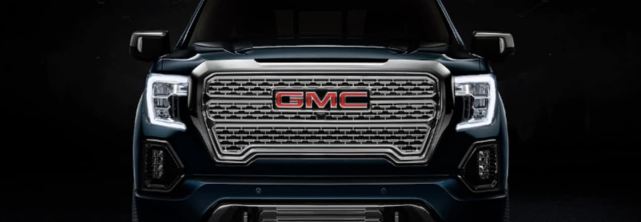 2019 GMC Sierra 1500 Denali in black parked showing the grill and LED headlights.