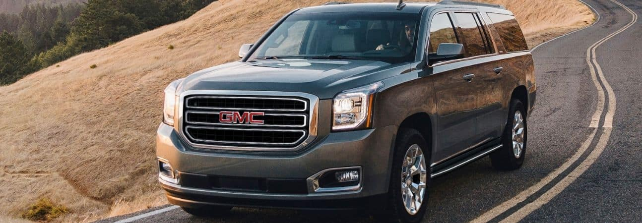 2020 gmc yukon driving down a winding road