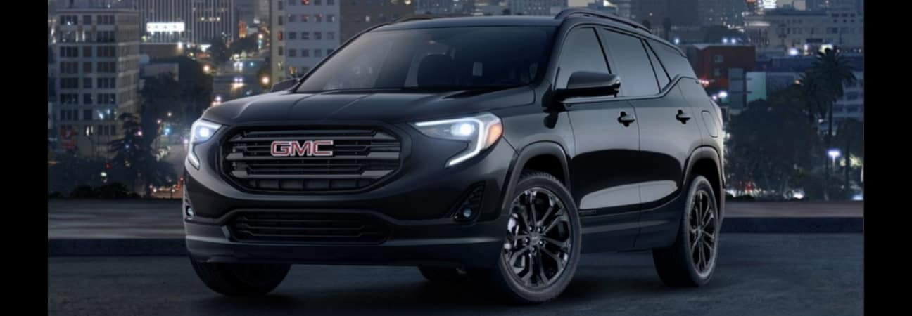 A black 2019 GMC Terrain parked in front of a city skyline