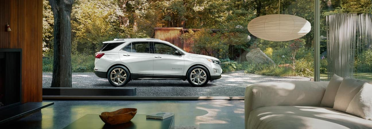 2019 Chevrolet Equinox in pearl white parked outside of a modern home