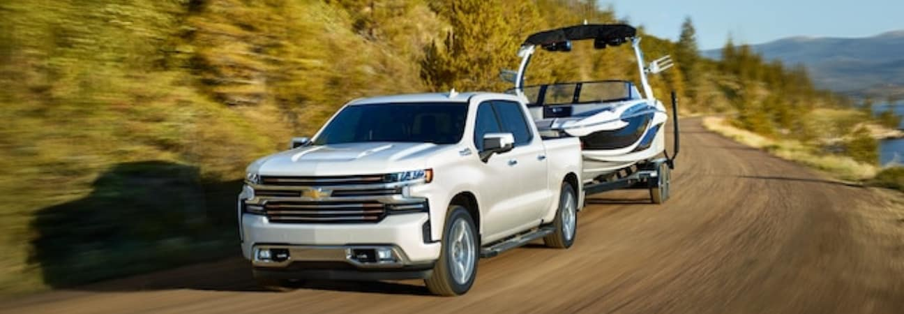 2019 Chevrolet Silverado 1500 in white hauling a boat on a dirt road