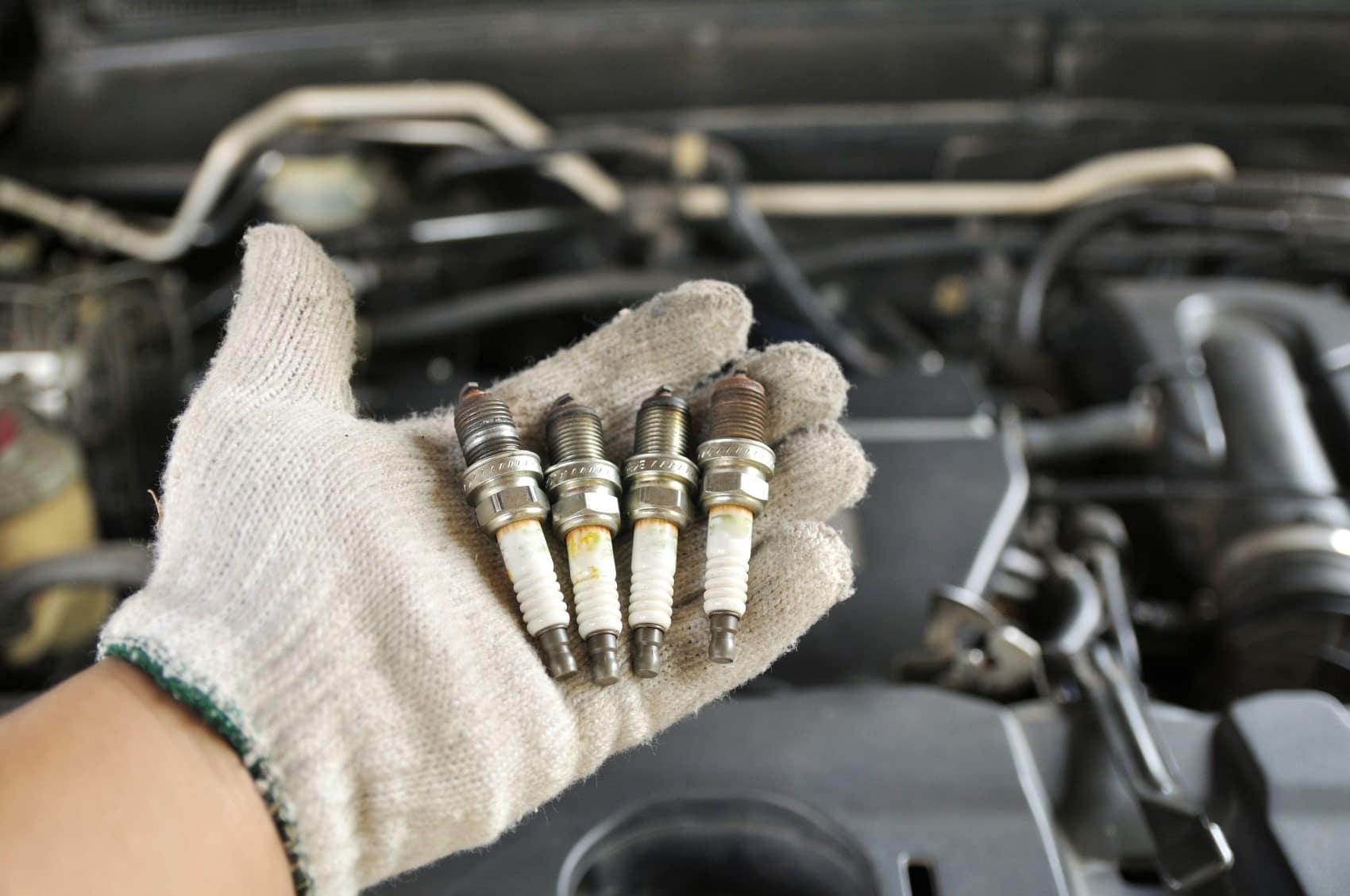 Technician holding new spark plugs under open hood