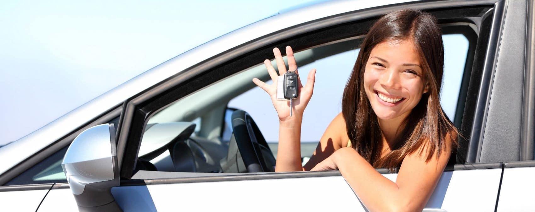 Woman in a rental car holding keys