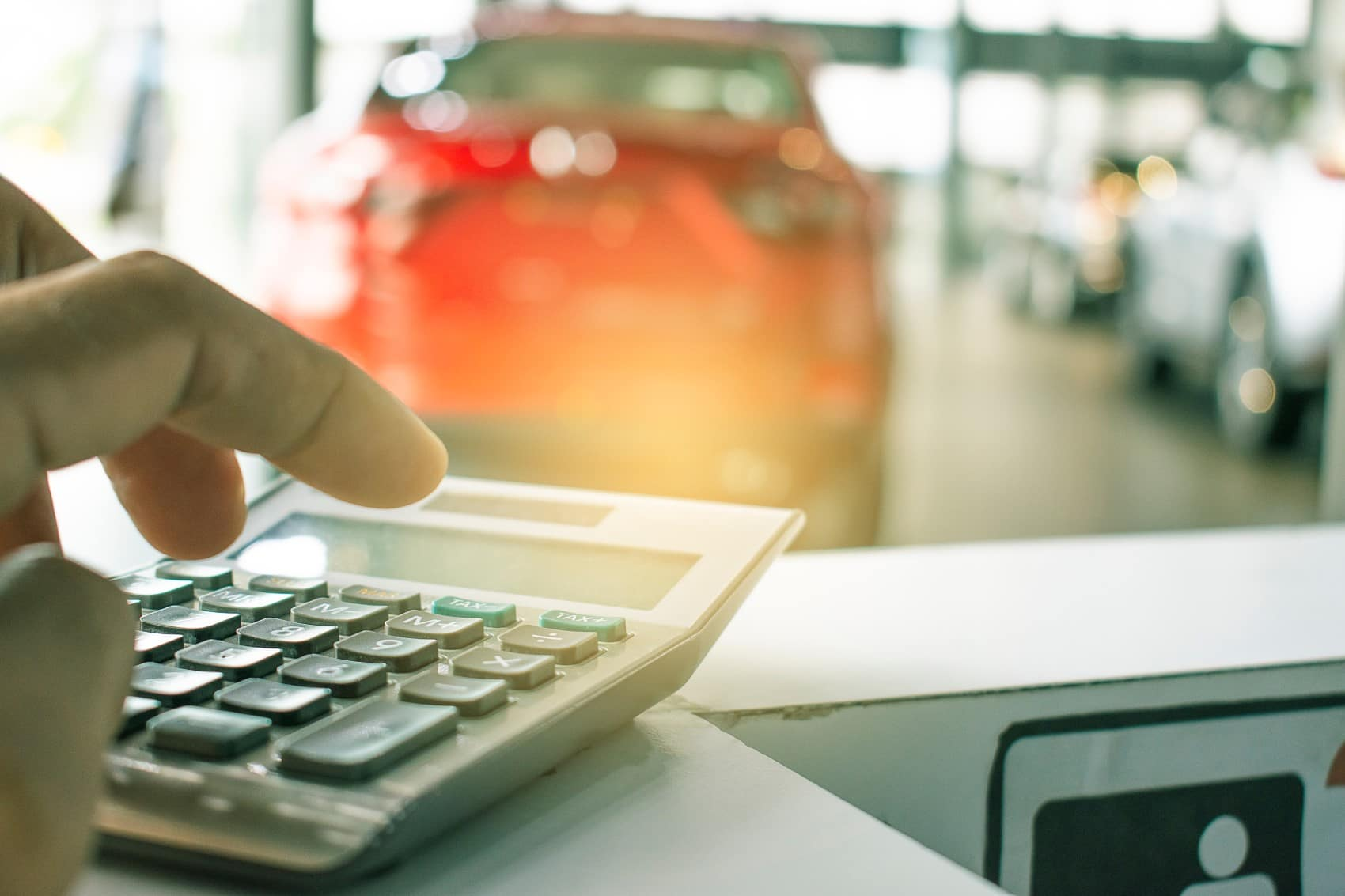 Person calculating car financing in dealership