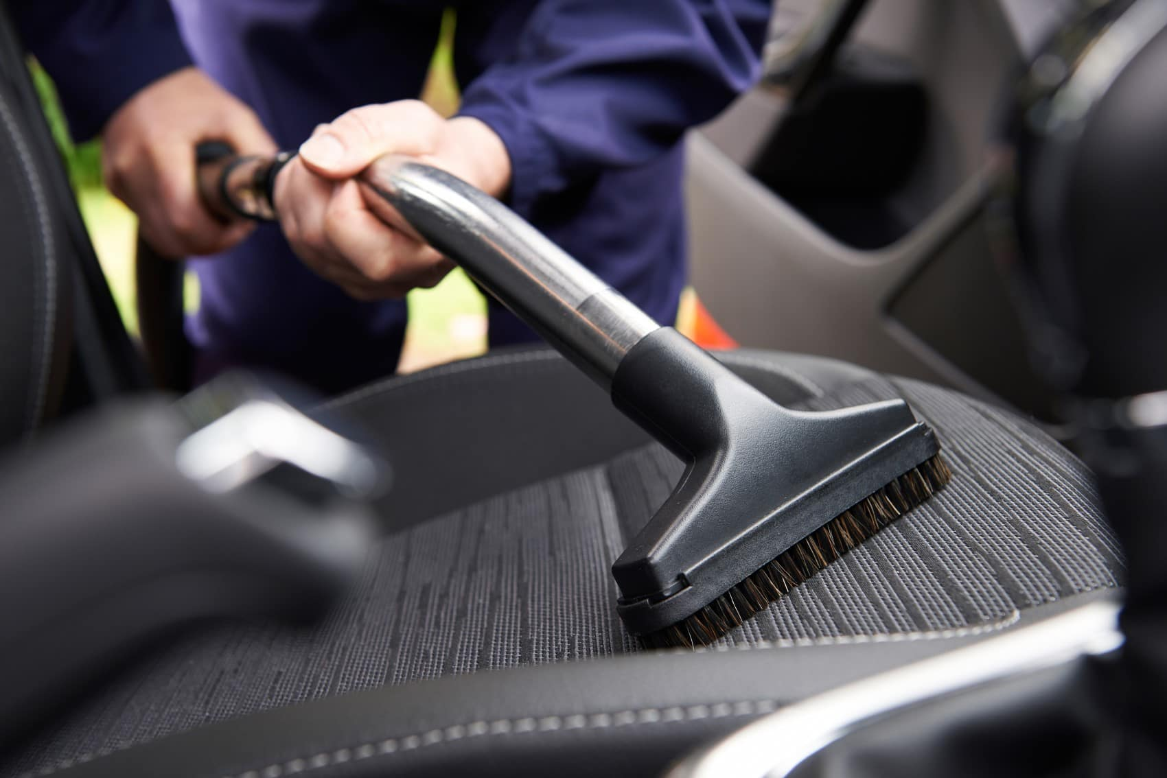 Person vacuuming out interior of vehicle