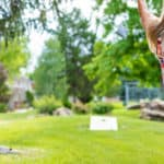 Female in focus in foreground Playing Bean Bag Toss Corn Hole Game