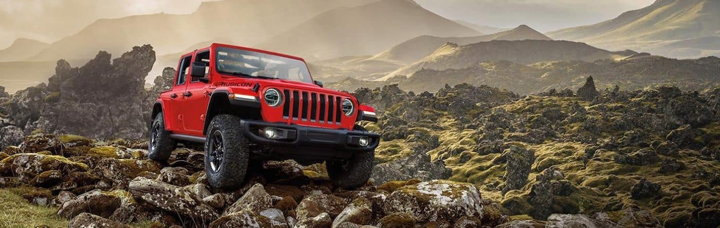 A 2020 Jeep Wrangler driving over boulders with mountains in the background