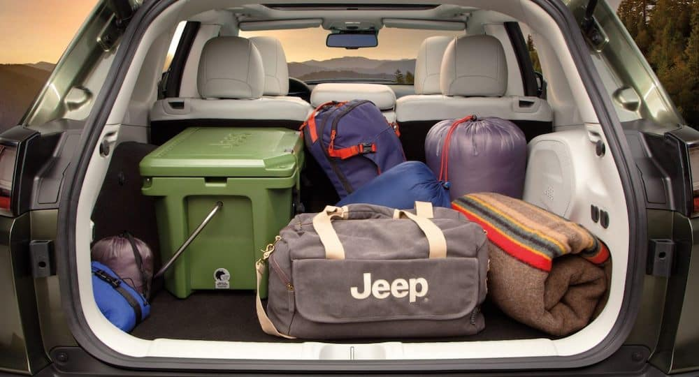 The spacious cargo area in a 2020 Jeep Cherokee interior filled with camping gear