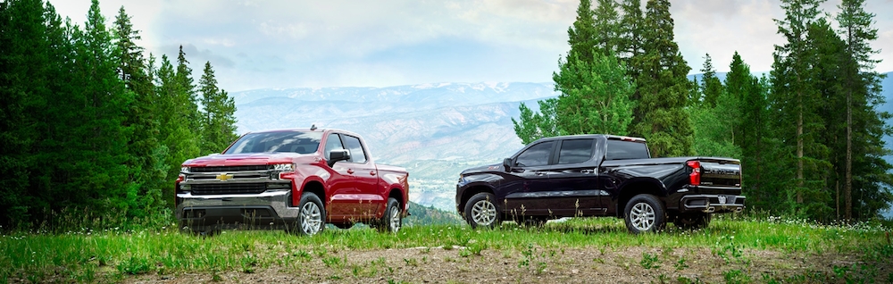 Two 2020 Chevy Silverado 1500 models parked with a mountain in the background