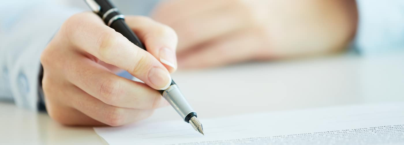 Mans Hand Reviewing a Liability Insurance Agreement