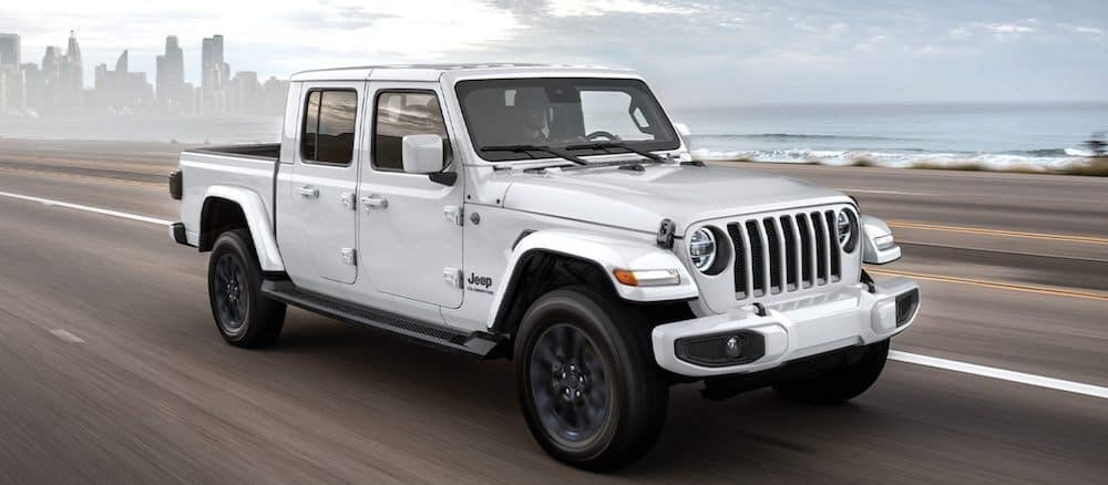 A 2020 Jeep Gladiator driving on a road with a city skyline in the background