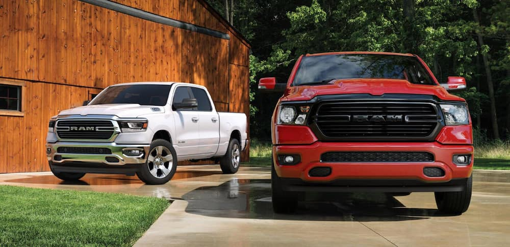 Two 2020 RAM 1500 models parked outside of a barn