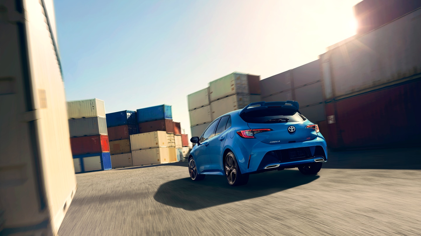 Toyota_Corolla_Hatchback_Blue_Driving_Rear_View