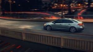 Toyota_Corolla_Driving_In_City_On_Bridge
