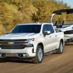 2020 Chevrolet Silverado 1500 towing boat on dirt road
