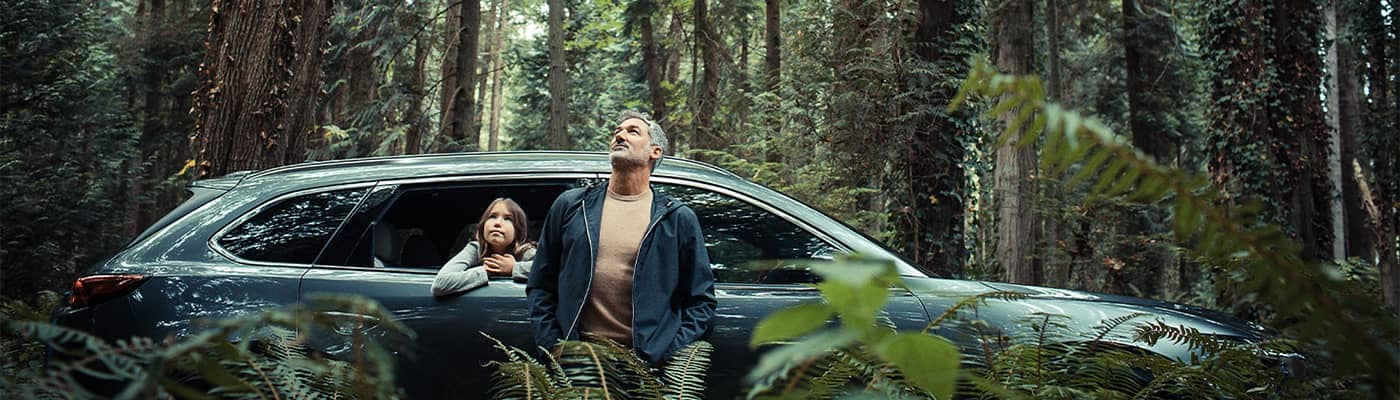 Man and daughter standing by Mazda CX-9 looking up at trees in forest