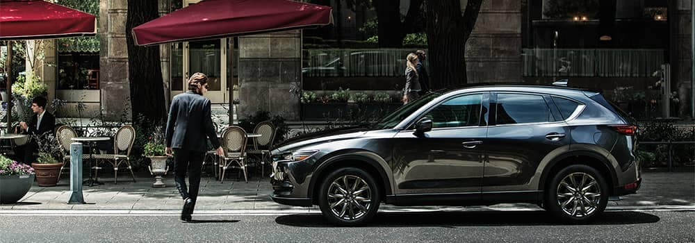Man Walking by a Mazda CX-5 Parked on Side of Road