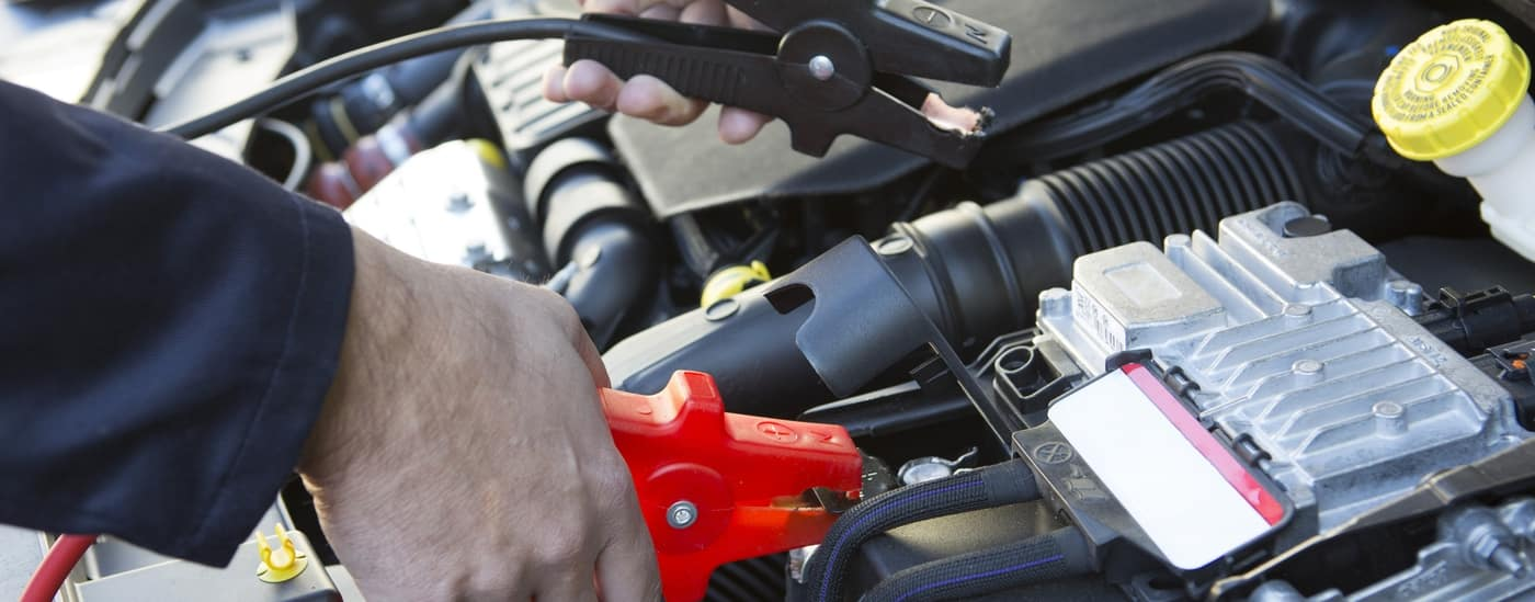 mechanic attaching jumper cables