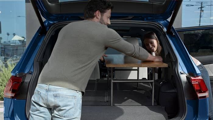 Couple loading table into cargo area of VW Tiguan