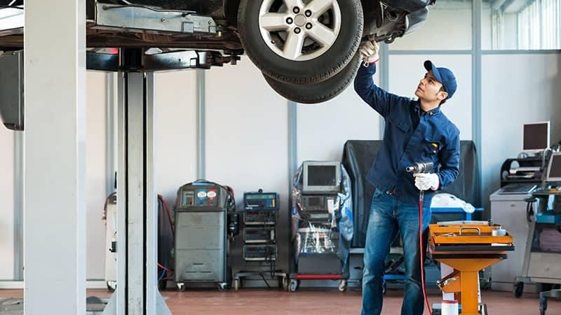 Mechanic working on car lifted