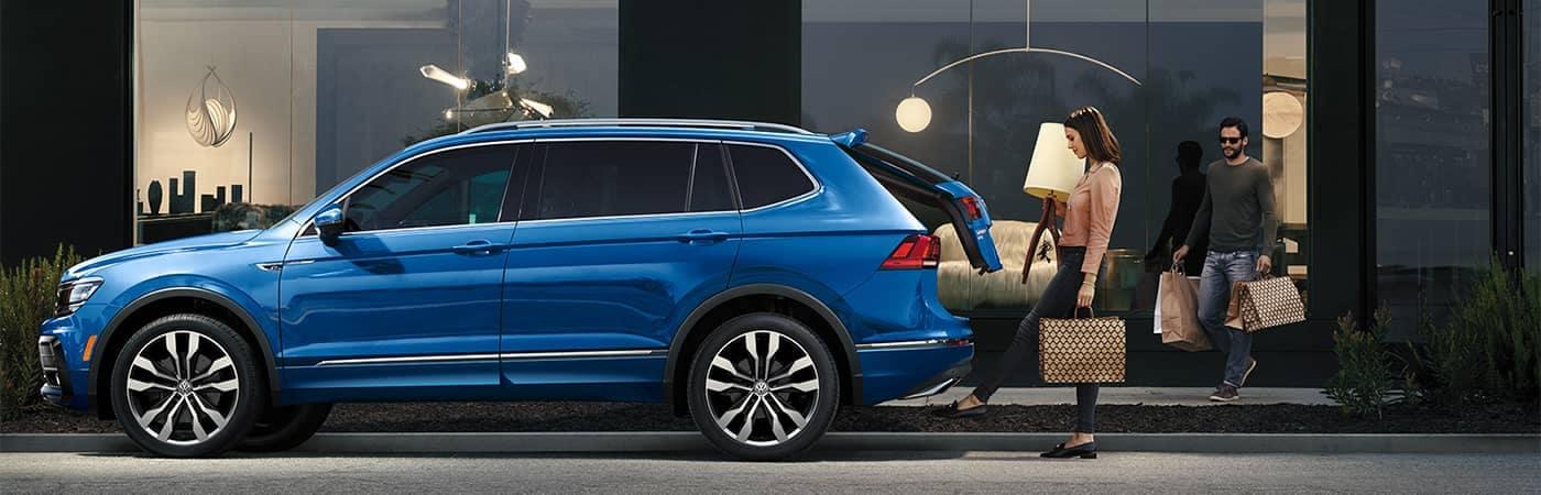 Couple loading stuff into back of Volkswagen Tiguan
